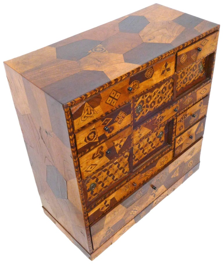 A wonderful and unusual handcrafted, Japanese marquetry cabinet. A fantastic, compact piece, thoroughly covered in a playful array of geometric designs; featuring drawers of various sizes as well as sliding-door compartments. Incredible execution