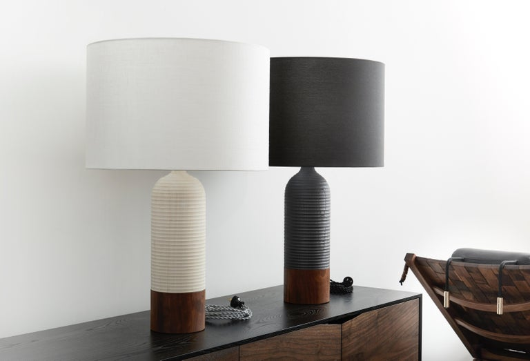 Handcrafted lamp of selected ash and walnut, laminated and turned on a lathe. Horizontal grooves are cut into the surface to intersect with the vertical grain patterns of the tree's growth rings. Stainless steel finial, silver rayon twist cord,