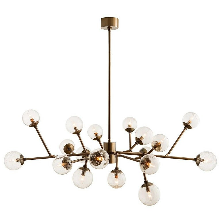 Contemporary 18-Light branching chandelier inspired by an iconic era. True to that time, yet authentic to its own modern spirit, shown with small clear tubular bulbs perched on brass arms with antique finish. 12 out of 18 arms are adjustable, making