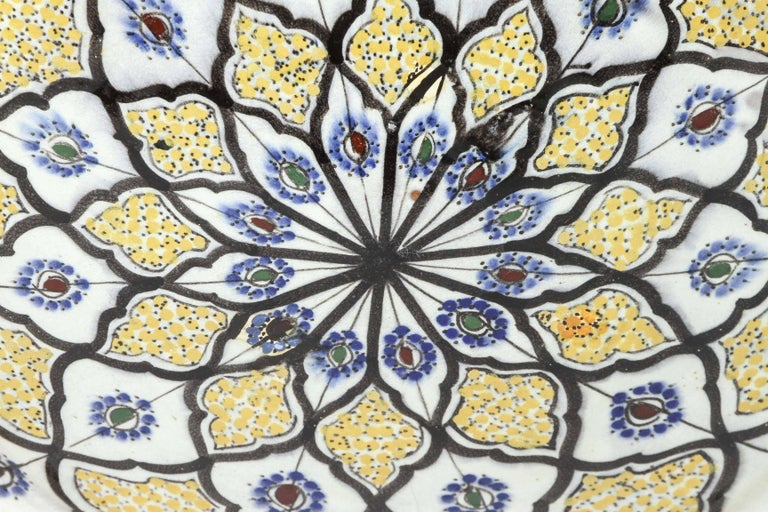 """Large Handcrafted Moroccan hand-painted glazed ceramic plate with a yellow background and adorned with geometric blue and black Moorish designs. The Moroccan large charger is signed in the back in Arabic """"Safi"""