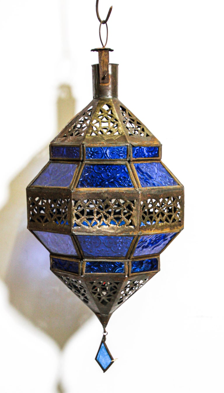 Moroccan metal and blue glass lantern in diamond shape. Moroccan lantern in octagonal shape with rust color metal finish and blue glass. The top and bottom  with open metal work Moorish design. This Moroccan lantern when lit will cast light on the