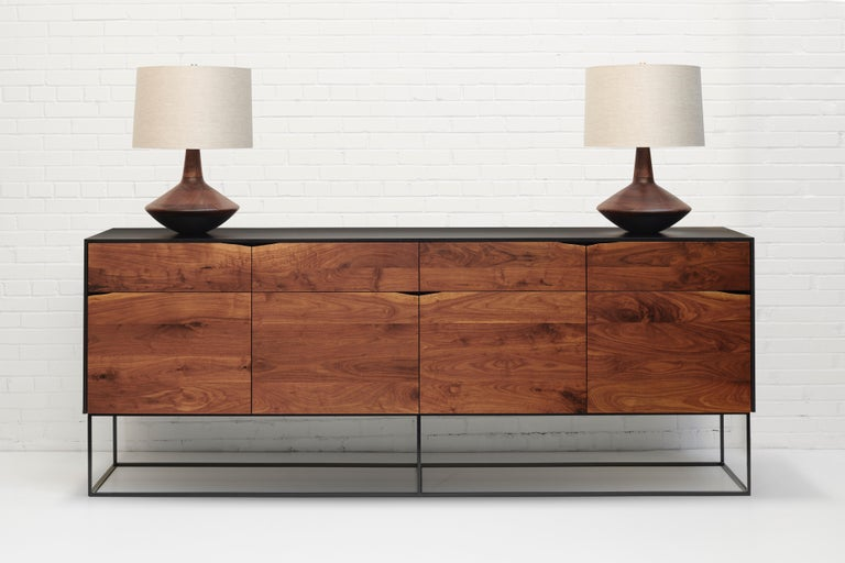 Handcrafted sideboard of select American hardwoods with black steel base. Black lacquered ash cabinet with four walnut soft-closing doors and four dovetailed walnut drawers with live-edge wane pulls. Each compartment has an adjustable shelf. Great
