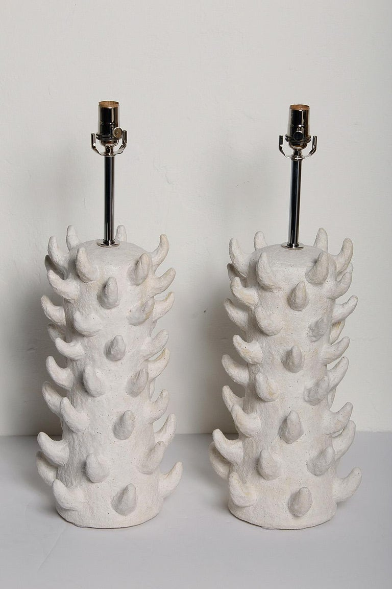 Pair of custom white salt-glazed stoneware lamps, handcrafted exclusively for Stripe by ceramicist Priscilla Hollingsworth. Polished nickel hardware with white fabric cords. Height measurement below is to top of socket.