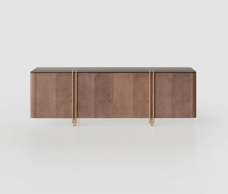 A contemporary minimal design crafted of sycamore maple wood and aged brass handles and legs. The piece features crystal grey glass top. Glossy grey sycamore. Legs: Old brass-plated steel. Top: Grey mirror.