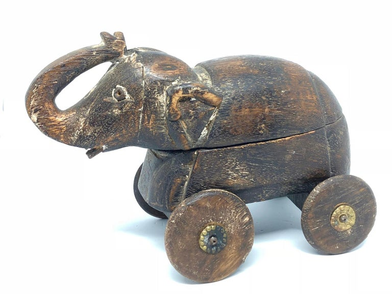 A rustic and weathered carving of an elephant probably used as a pull toy or just a display item with a secret chamber. Extensive wear with some loss. A charming rustic and eccentric piece. We think it is from Thailand and was made circa 1950s.