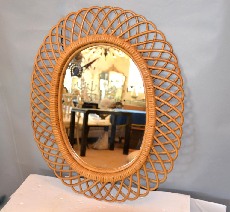 Vintage handcrafted oval bent rattan mirror. The back is covered in red velvet. This mirror is super fashionable.