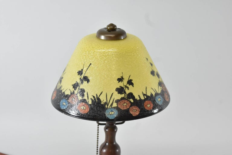 A beautiful Handel reverse painted boudoir lamp. This lovely lamp features an exterior reverse painted floral scene in shades or yellow with a black border and multi-color poppies. The base has a nice patina. Measure: The lamp is 14