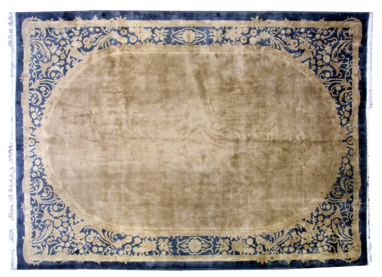 Handmade antique Art Deco Chinese rug in original condition. The rug is in soft beige shade with all-over design. Decorative border around is in blue shade. The wool is very soft. The rug is in original good condition.