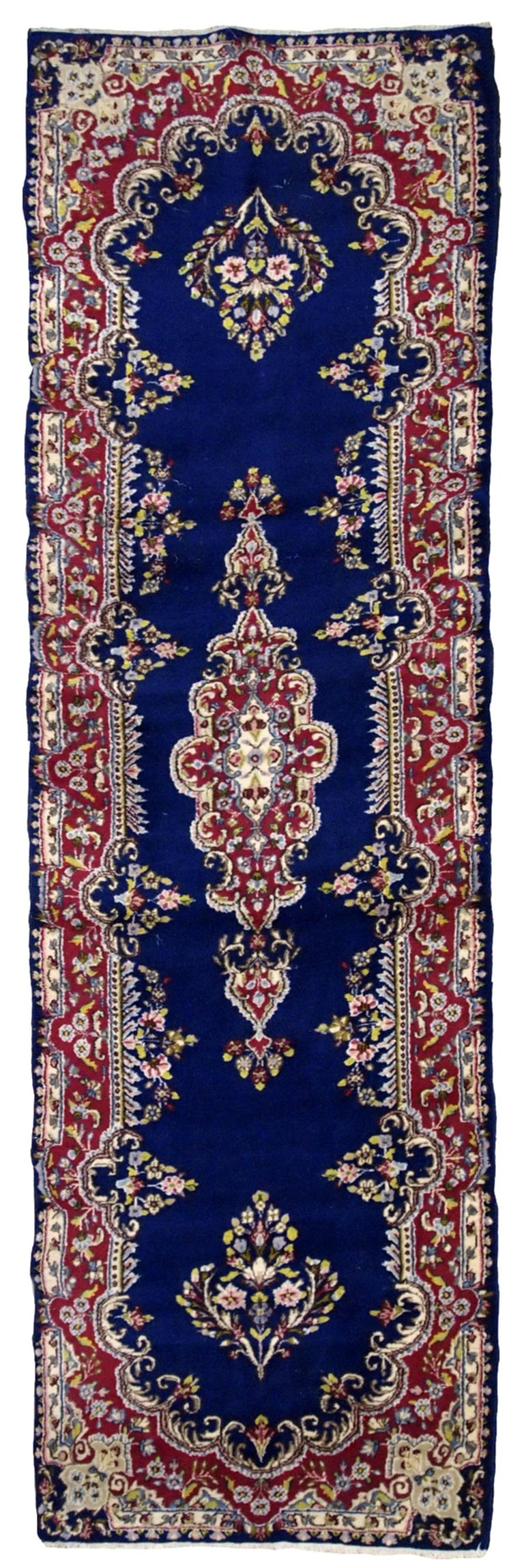 Handmade antique Persian Kerman runner in bright blue and red wool. The runner is from the middle of 20th century in original good condition.