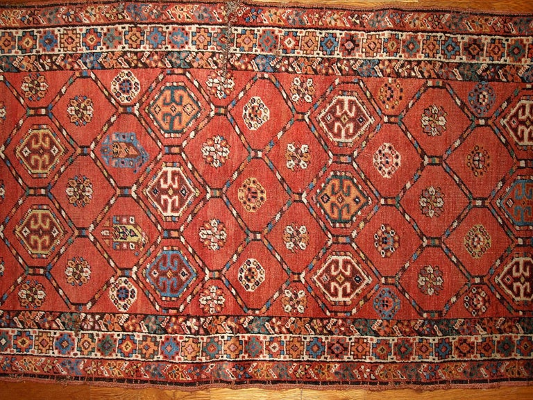 Antique handmade Kurdish runner in bright red color. The rug has one cut on the side and damaged corner with several small holes. Measures: 3.2' x 12.2' (97cm x 371cm).