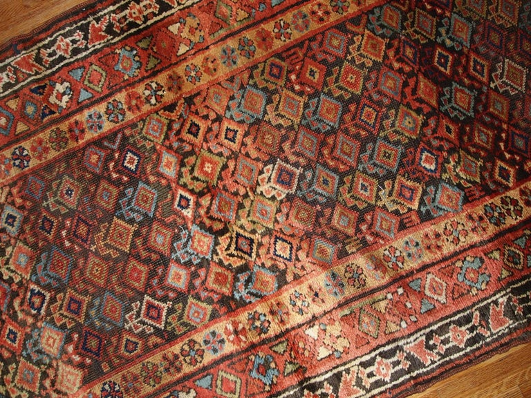 Antique handmade Kurdish runner in traditional geometric design all over the chocolate brown field. The rug is from the end of 19th century in original good condition. Measures: 3.6' x 17.8' (109 cm x 542 cm).