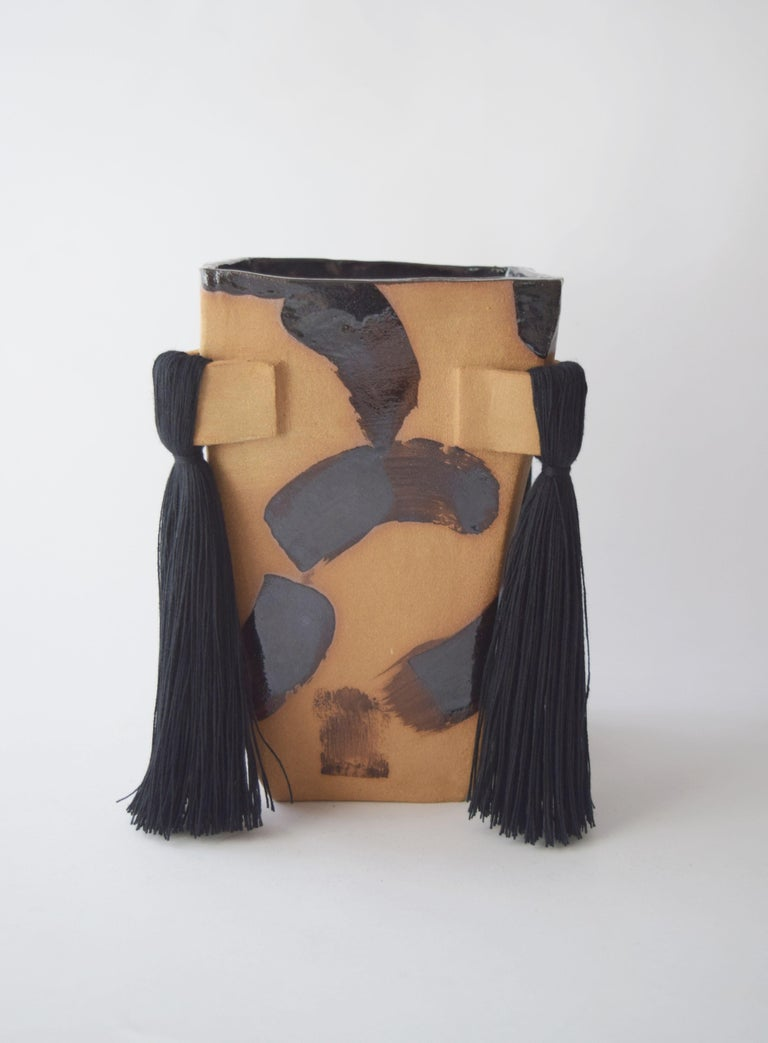 Vase #640 by Karen Gayle Tinney  Hand formed stoneware vase made in dark natural clay with hand painted black brushstroke artwork painted on outside. This inside is glazed black. Vessel will hold water but care should be taken not to damage fiber