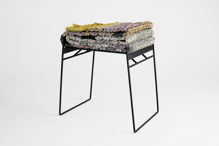 The iota rug stool is a matte black iron stool covered by a multicolored tailored rug for comfortable sitting. The rug can be imaginatively arranged in different shapes which create altering appearances and different space occupations. The rug is