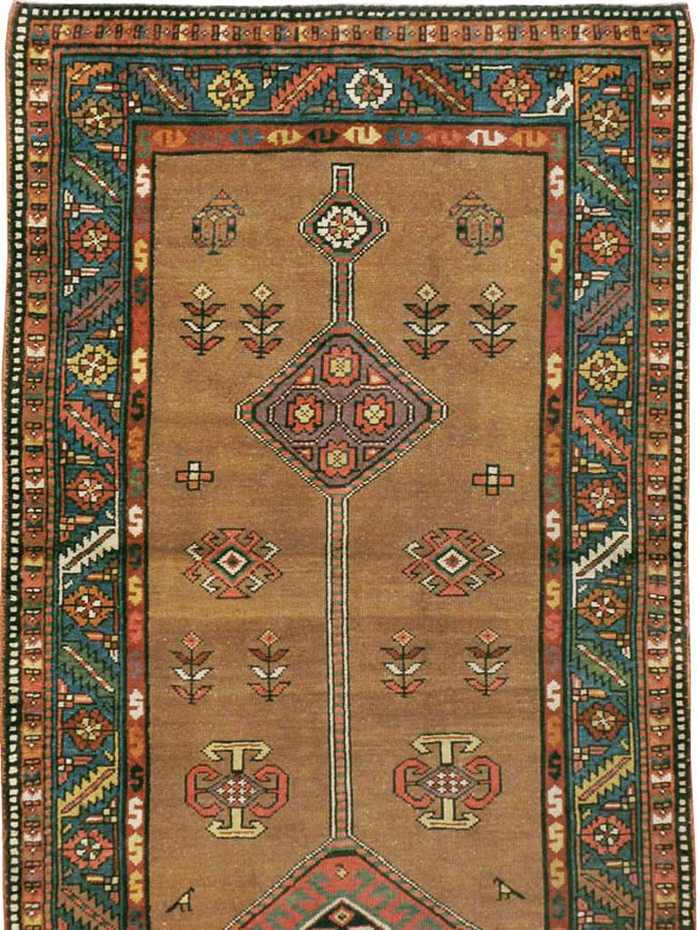 An antique Persian Serab rug in runner format from the early 20th century. The warm camel-tone brown field spaciously displays a long pole medallion punctuated by geometric lozenges, with stylized small flowers and rustic animals scattered about.