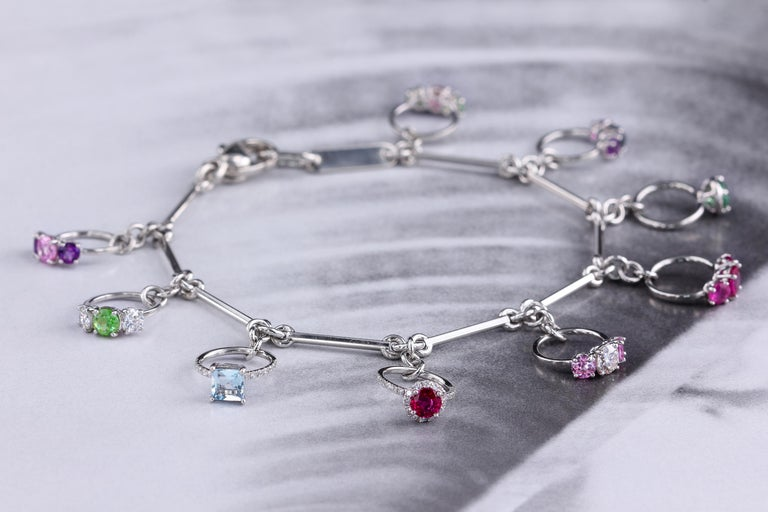Platinum bracelet with nine charms, each charm is a unique miniature ring set with natural gemstones and diamonds. Approx. 6.5 inches long, solid hand forged platinum. Each charm is handmade and completely unique. The design won the 2012 Platinum