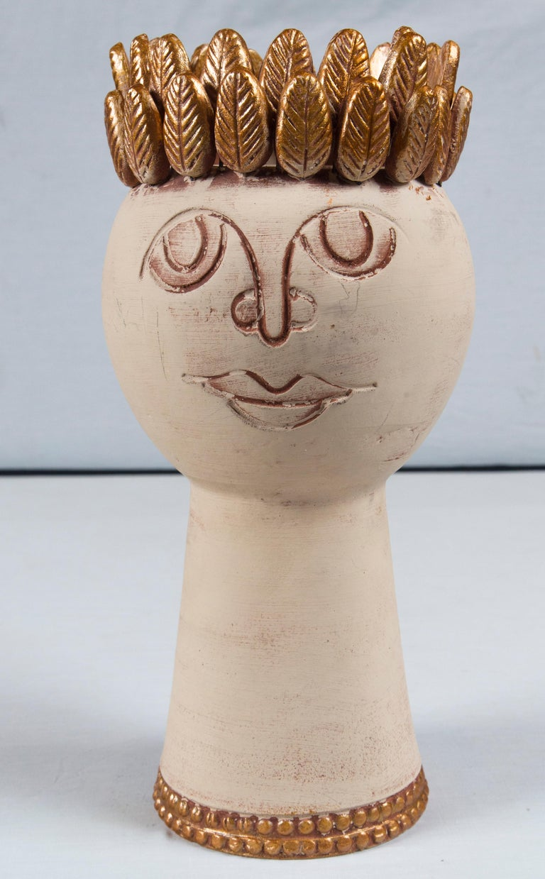 Handmade pottery head vessel, off-white and bronze colored with a bronze laurel leaf crown.
