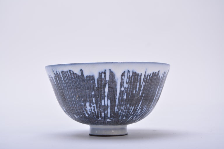 A handmade Swedish Mid-Century Modern ceramic bowl with green, blue, brown, and dark grey glaze creating a geometric pattern. Exterior of the bowl has been decorated with the sgraffito technique that consists of fine lines carved into the background
