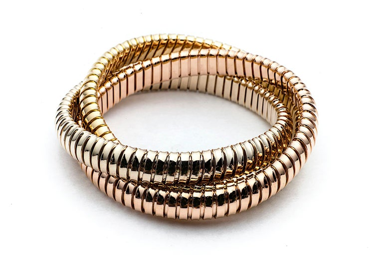 With a timeless but modern style, this chic intertwined three strand 9mm tubogas rolling bangle bracelet was originally inspired by the flexible automotive gas tubing of the 1920's.  Translated into luxurious 18 karat white, rose and yellow gold
