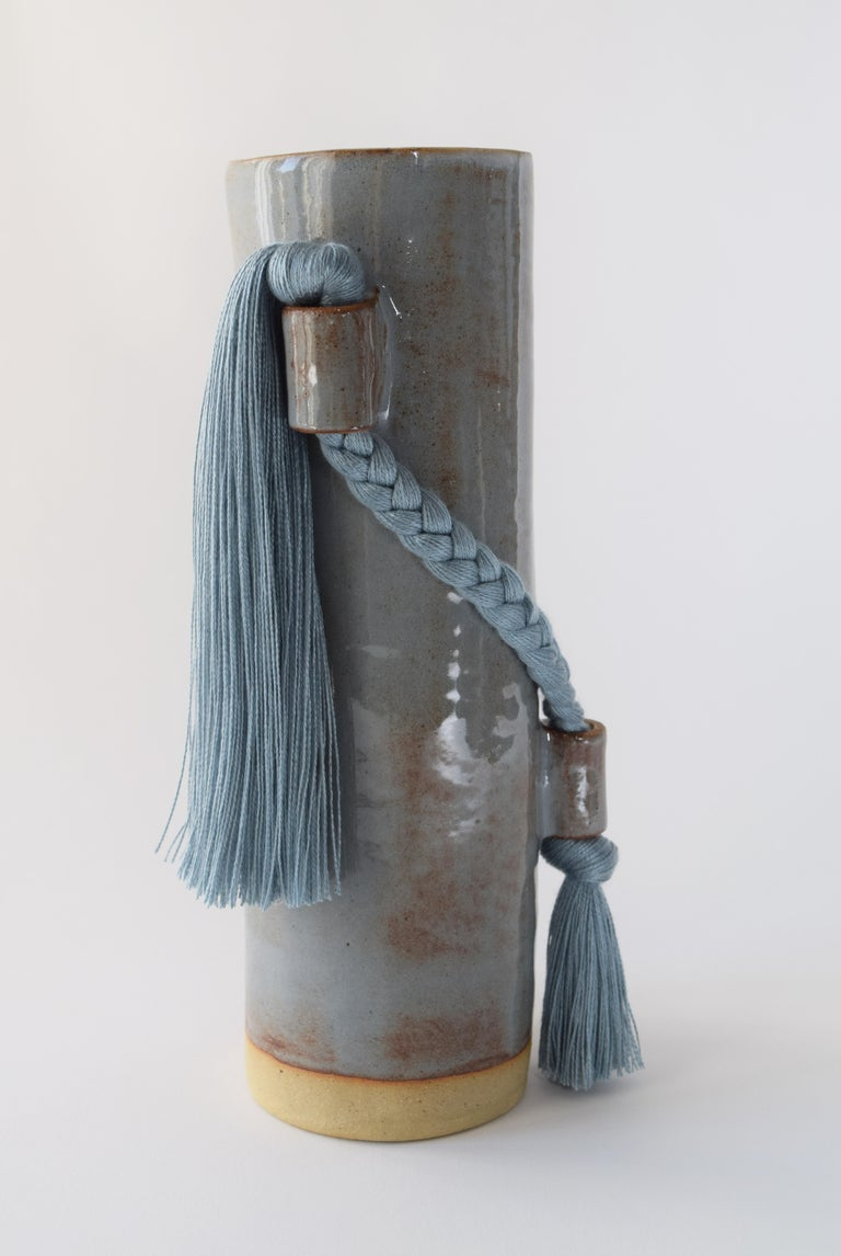 Vase #695 by Karen Gayle Tinney  Hand formed stoneware vase with blue shino glaze. Inside is glazed white and will hold water - please take care not to damage fringe areas. A blue tencel braid with fringe is applied to the outside of the vase. This