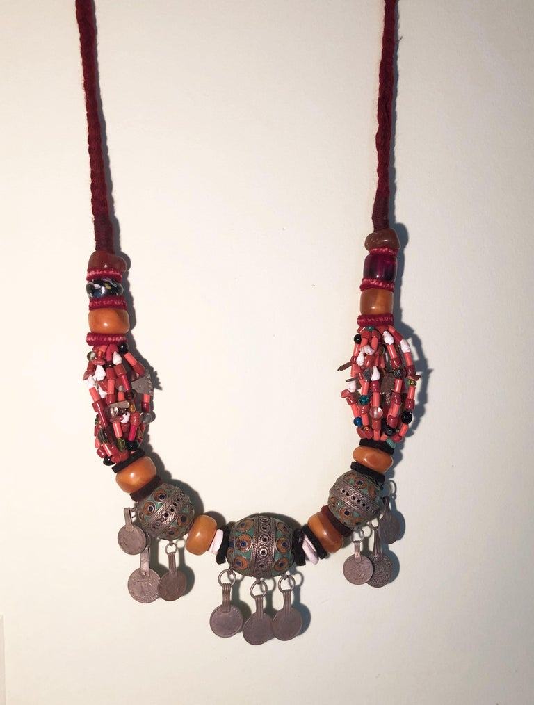 Handmade artisan pendant necklace from Morocco. Made in the southern desert town of Zagora, this necklace has many precious beads including coral, glass, amber copal resin, shells, onyx, and more. Numerous silver charms & hamsa hand of fatima good