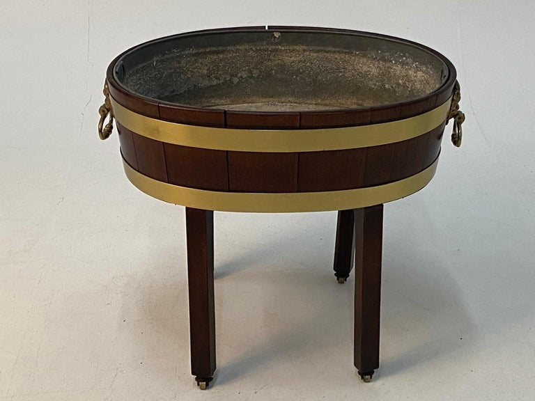 A beautiful antique English Georgian style oval mahogany cellarette on stand having handsome brass banding and figural handles with detailed lion or gargoyle-esque hardware. Legs terminate in brass casters and original metal liner is