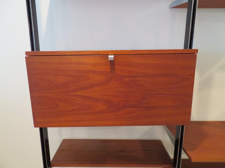 Handsome George Nelson for Herman Miller CSS 3 bay wall unit. This wonderful set consists of 2 flip down cabinets, 8 adjustable shelves, 1 desk shelf and 4 gunmetal finish poles along with all necessary hardware for tension installation. The set