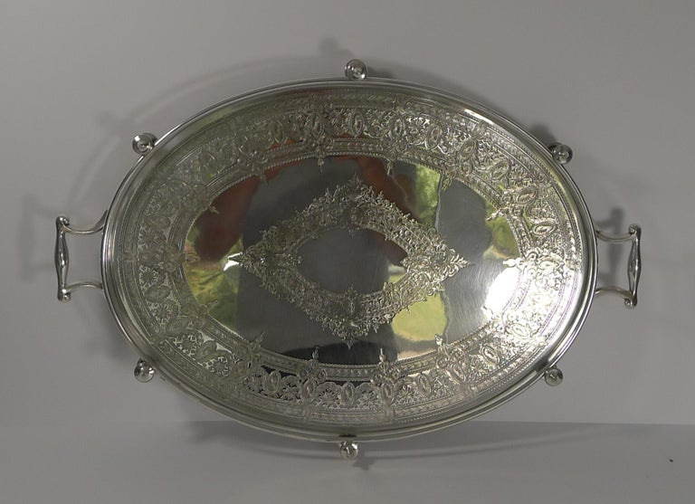 A hefty and very sold tray made from EPNS (Electro-Plated Nickel Silver) by the renowned silversmith, James Dixon and Sons, with full marks on the underside.  The base of this galleried tray is beautifully engraved, highly decorative.  Dating to