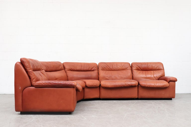 Handsome De Sede 5-piece cognac leather sectional sofa. Beautiful patina, thick leather. In original condition with visible wear. Minimal stains and two small tears on a cushion back as well as a very worn back corner spot (pictured). All signs of