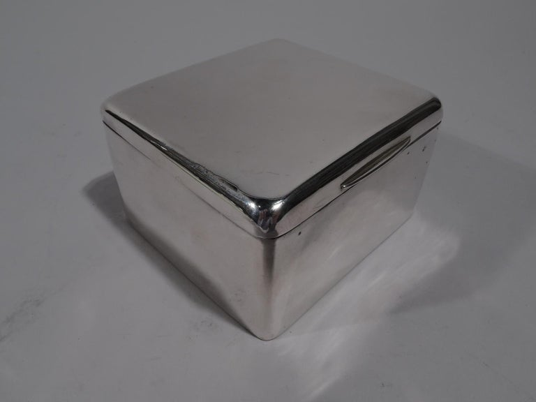 Edwardian sterling silver box. Made by Arthur & John Zimmerman in Birmingham in 1904. Square with hinged and tabbed cover. Box interior cedar lined. Cover interior gilt. Box underside leather lined. A handsome receptacle for rings and cufflinks.