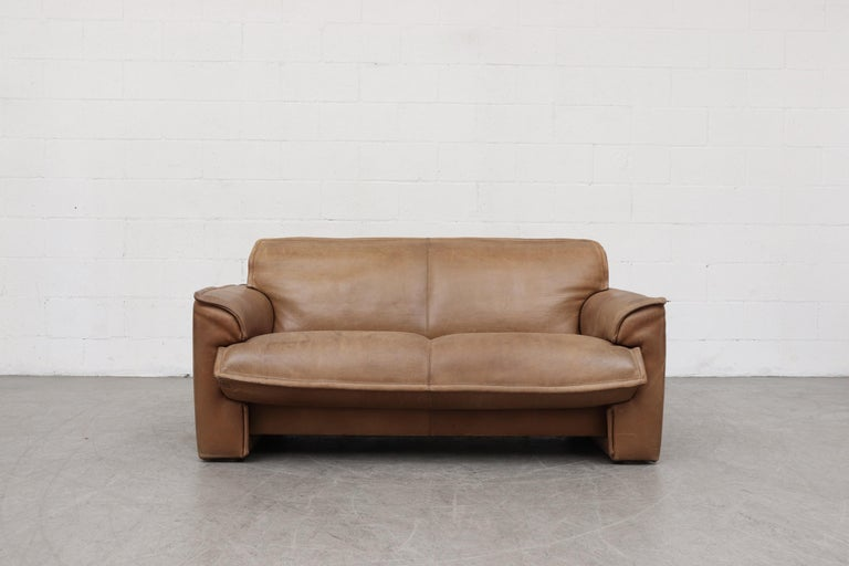 Leolux Buffalo leather love seat sofa in very original condition with heavy patina and visible signs of wear. Other similar sofas available in this color tone a with heavier patina and others in darker leather, listed separately. Actual color may