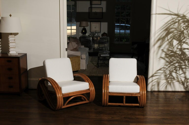 A stellar restored pair of adjustable back Pretzel lounge or club chairs, circa 1950. Expertly crafted three-band rattan and hardwood construction. Stout, sturdy and comfortable - designed and intended for heavy regular use. The pair have mellowed