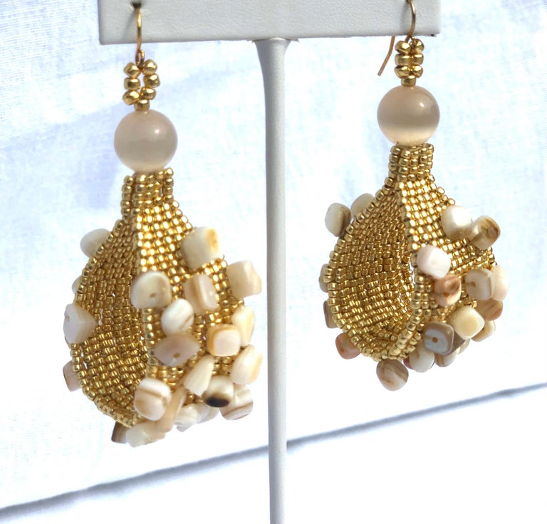Handwoven gold plated seed bead Conchita hoop earrings with conch shell chip beads.