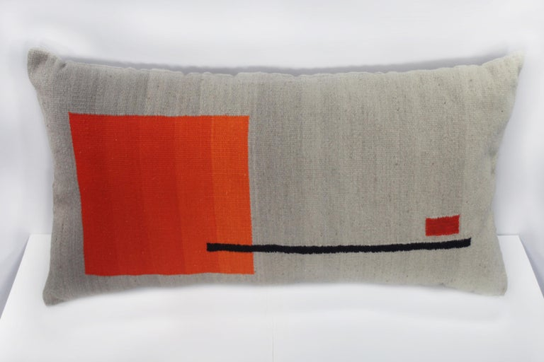 Contemporary handwoven wool throw pillow in red, orange and grey. 