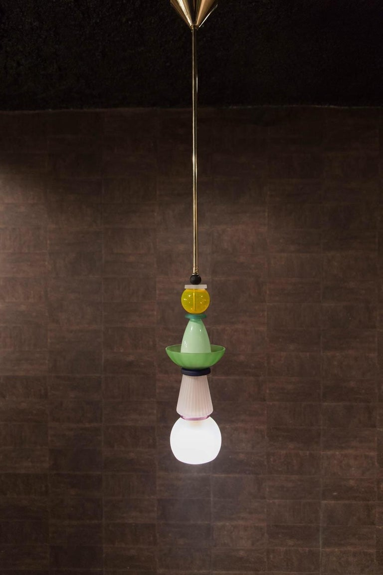 The original name of this traditional type of hanging lamp from Venice is cesendello. Our hanging lamp is made of hand blown colored glass vase components in yellow, green, pale pink, black, white, and matt mounted on a gold metal bar. They have