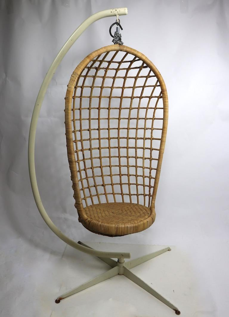 Groovy hanging wicker egg chair with heavy cast iron and steel base. The wicker chair hangs from a coil spring giving it flex when you sit. It comes with additional chain and hook if you choose to hang it from the ceiling rather than the metal