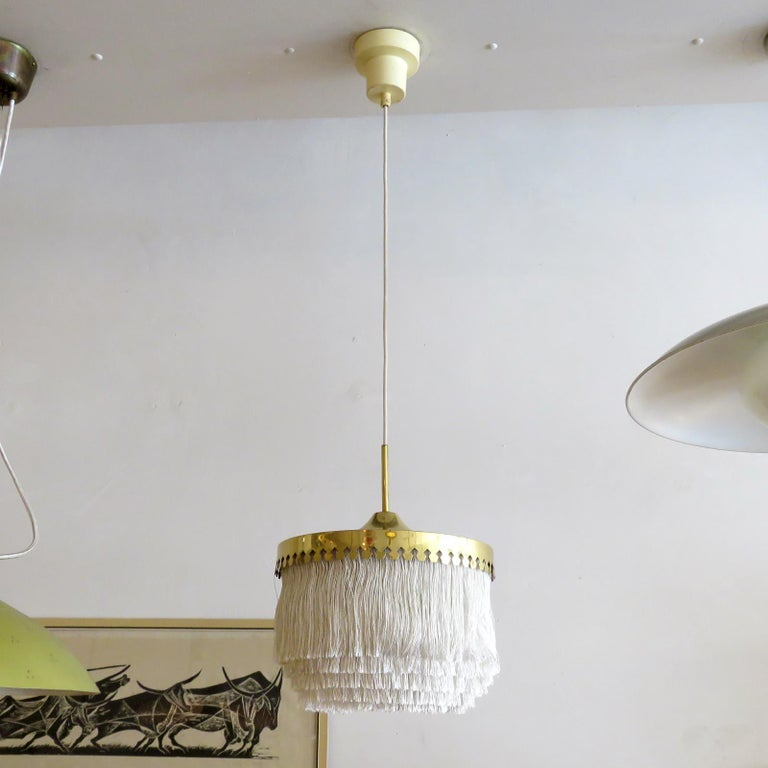 Wonderful pendant lamp by Hans-Agne Jakobsson for Markaryd, Sweden, 1960, with five tiers of off-white fringe silk cord with brass hardware frame and original white canopy. Overall drop can be customized. Custom back plate for US j-boxes, wired for