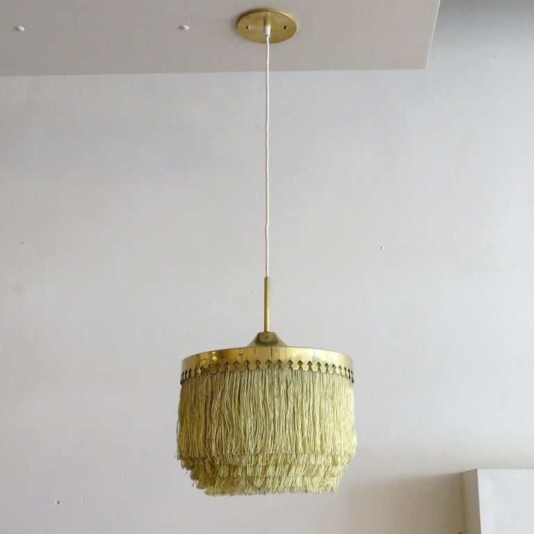 Wonderful pendant lamp by Hans-Agne Jakobsson for Markaryd, Sweden, 1960, with five tiers of off-white fringe silk cord with brass hardware frame and original white canopy. Overall drop can be customized, wired for US standards, one E27 socket, max.