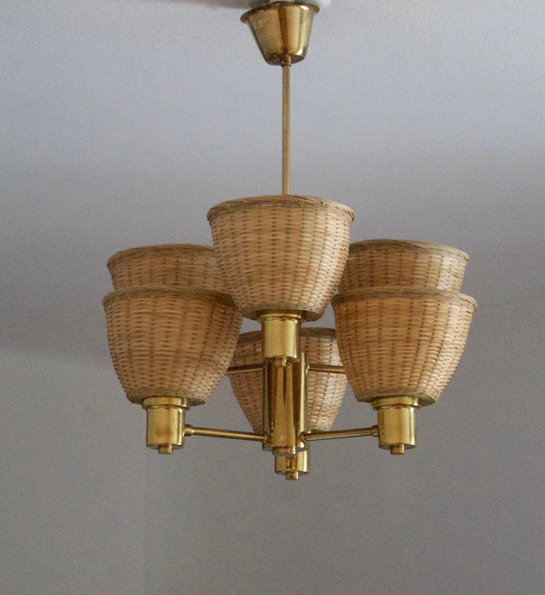 A chandelier, design attributed to Hans-Agne Jakobsson. Presumably by his own firm in Markaryd, Sweden. c. 1960s. Unmarked.  Assorted vintage rattan lampshades.