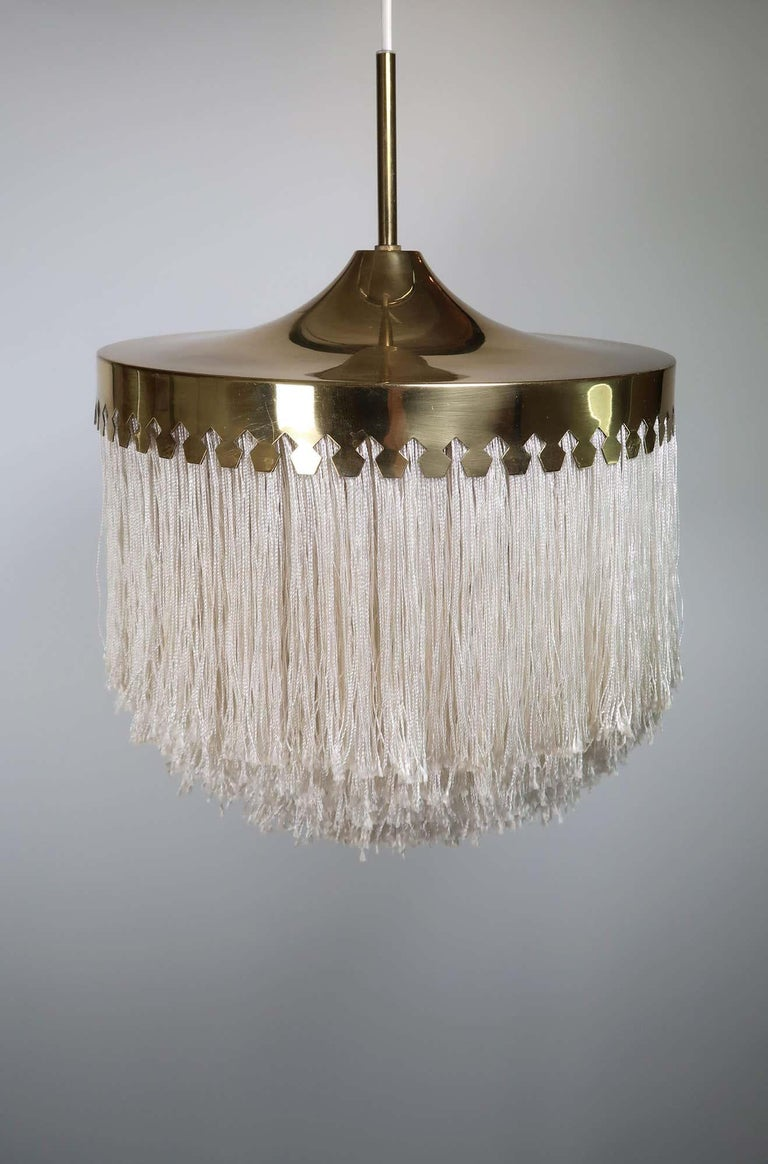 Original Hans-Agne Jakobsson pendant with cut brass canopy and cream silk fringes. Wonderful condition. This version has a beautifully designed shaped brass canopy on the bottom edge and 5 layers of silk fringe. Produced by Hans-Agne Jakobsson,