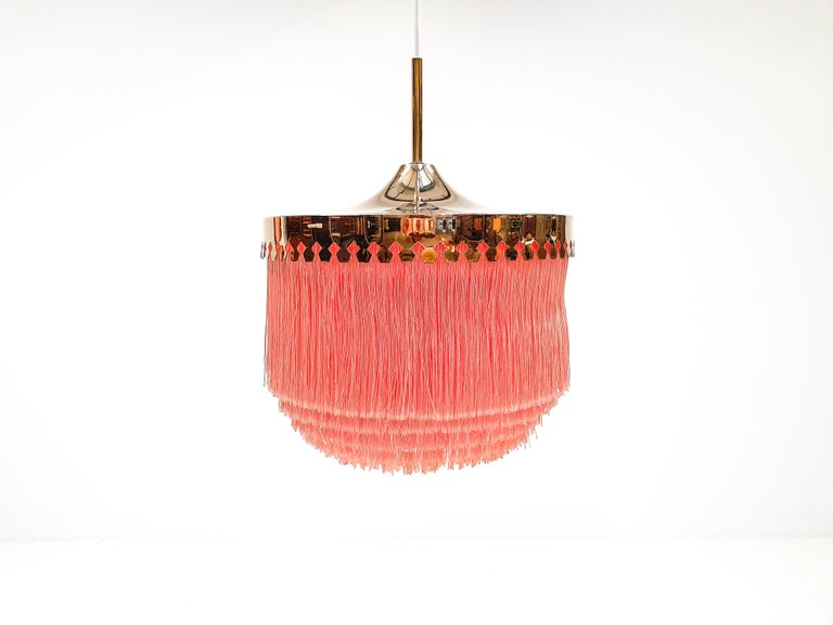 A Hans-Agne Jakobsson for Markaryd brass and ivory silk fringe model T601/M pendant, 1960s   A Hans-Agne Jakobsson for Markaryd pink colored silk fringed pendant with brass frame, dating from the 1960s.  Fully working, rewired, safety tested