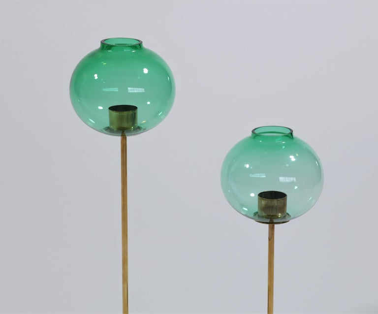 Elegant pair of candlesticks in brass and beautiful turquoise mouth-blown glass by Swedish designer Hans Agne Jakobsson. These candlesticks were manufactured by Swedish company
