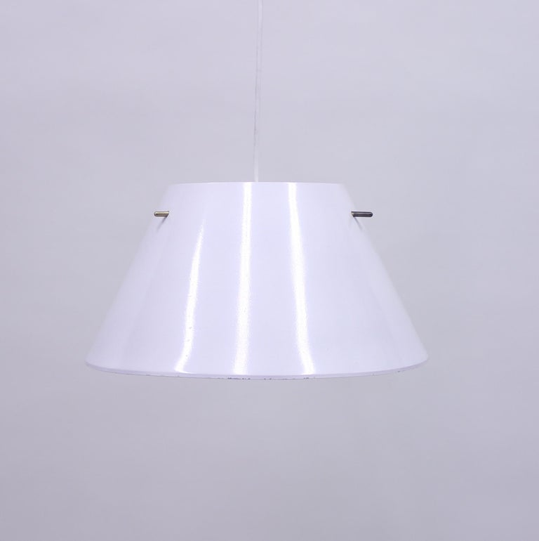 White sheet metal ceiling lamp with brass details produced by Hans-Agne Jakobsson AB. Good vintage condition with light ware. Marked with sticker from manufacturer.