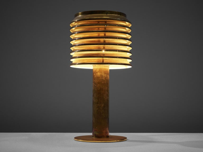 Hans-Agne Jakobsson, table lamp B-142, brass, Sweden, 1960s  This lamp features a brass foot that holds a brass shade. The shade consists of several layers, that create a rhythmic, atmospheric play of indirect light. Admirable patina adds even