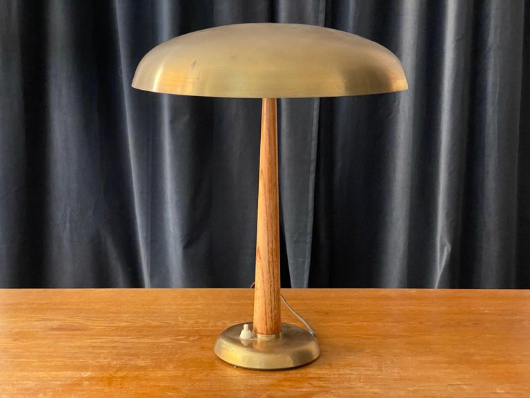 A 1940s functionalist table lamp / desk light. Swedish production label. Design attributed to Hans Bergström. Rod and base with similar proportions and configuration as documented Bergström models designed for Atelje Lyktan.  Executed in brass and