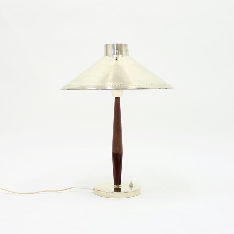 Teak and brass table lamp designed by Hans Bergström for ASEA in the 1950s. The shade is hold in place by three globe brass screws that sits on top of the shade as a decoration. Overall in a good vintage condition. All the brass has been polished