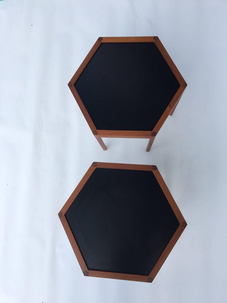 Hexagonal teak side tables by Hans Andersen for Artek with black Formica tops exposed joinery accents the design branded to the reverse