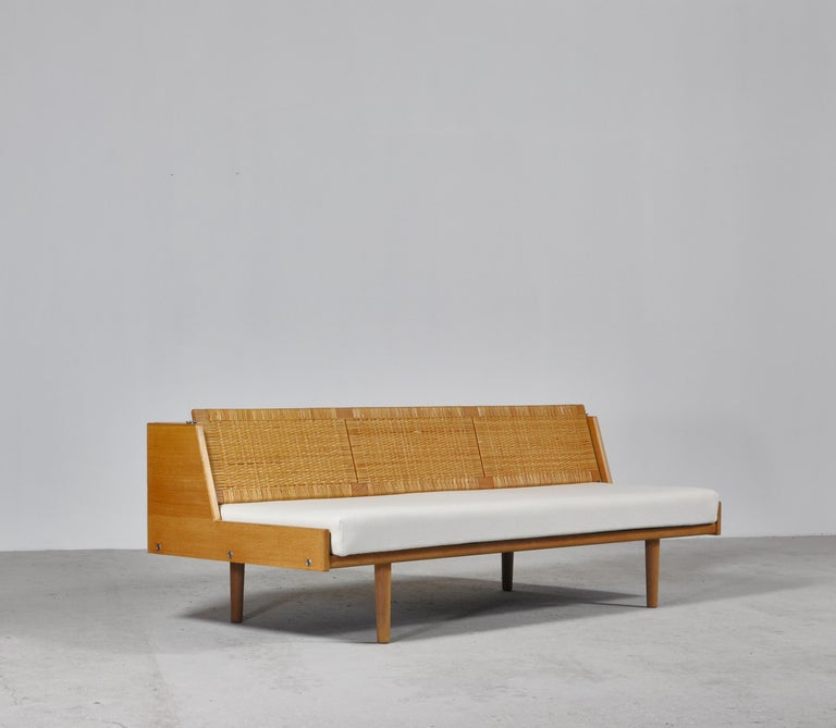 Designed by Hans Wegner for GETAMA this amazing convertible daybed / sofa features a beautifully patinated oak frame and woven cane / rattan back seat which reveals a hidden space for blankets, pillows etc. The model GE-7 was designed by Wegner in
