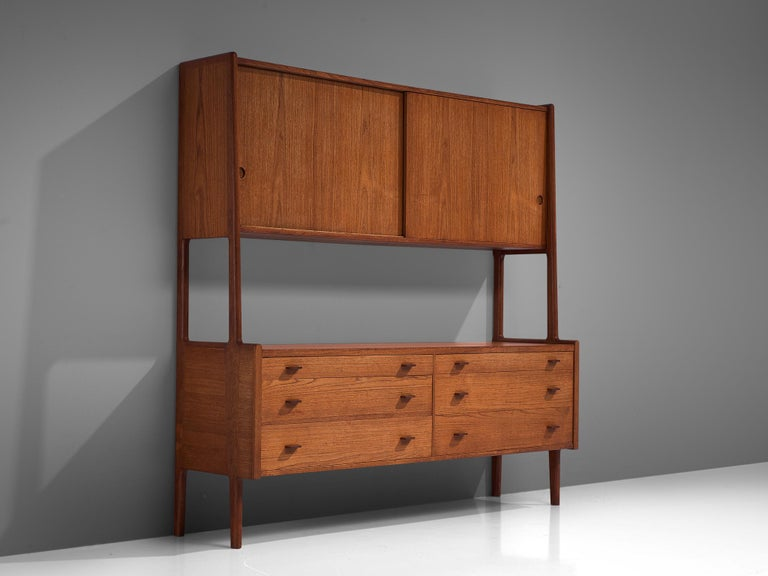 Hans Wegner for Ry Møbler, cabinet RY20, teak, Denmark, 1950s.  This cabinet is executed in teak and is typical for midcentury Scandinavian design. The cabinet features a base with four cylindrical legs that function as connective elements for the