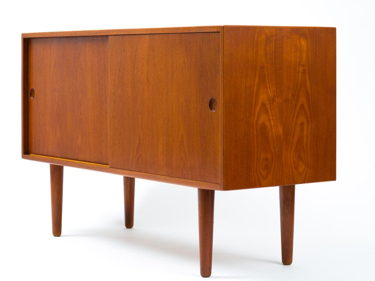 Fine and rare sideboard designed by Hans Wegner and built by eminent Danish cabinetmaker, Johannes Hansen. A pair of doors with integrated pulls conceal two adjustable shelves to the left and five adjustable drawers to the right. The case bears
