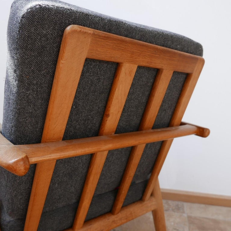 A smart armchairs by design legend Hans J. Wegner.   Denmark, circa 1955-1965.   Solid oak, original upholstery which is perfectly usable but has some signs of age, can be updated in house at cost.   Good condition and timeless comfortable